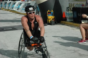Crossing finish line in racing wheelchair at 2013 Bone Island Triathlon Half-Ironman.